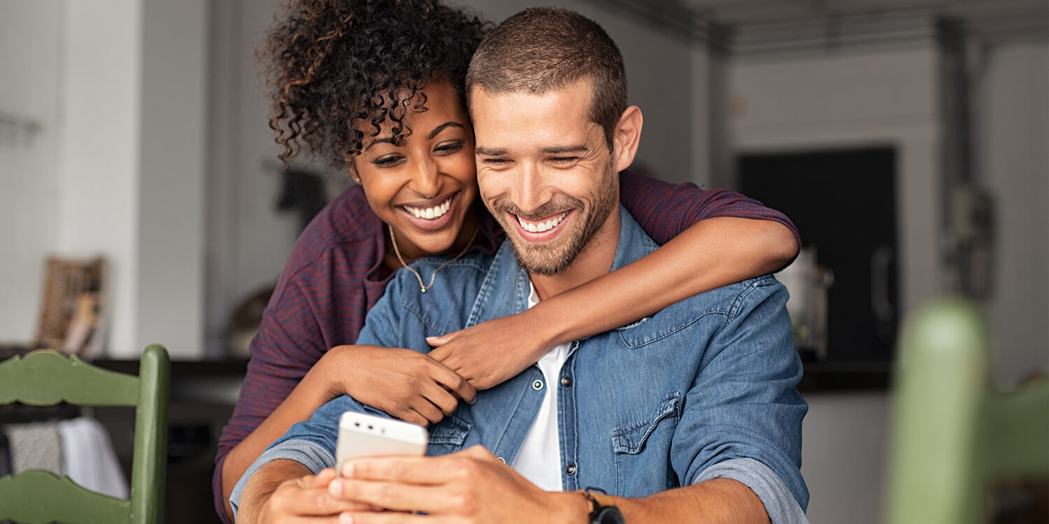 Smiling young couple hugging each other while looking at a smartphone.