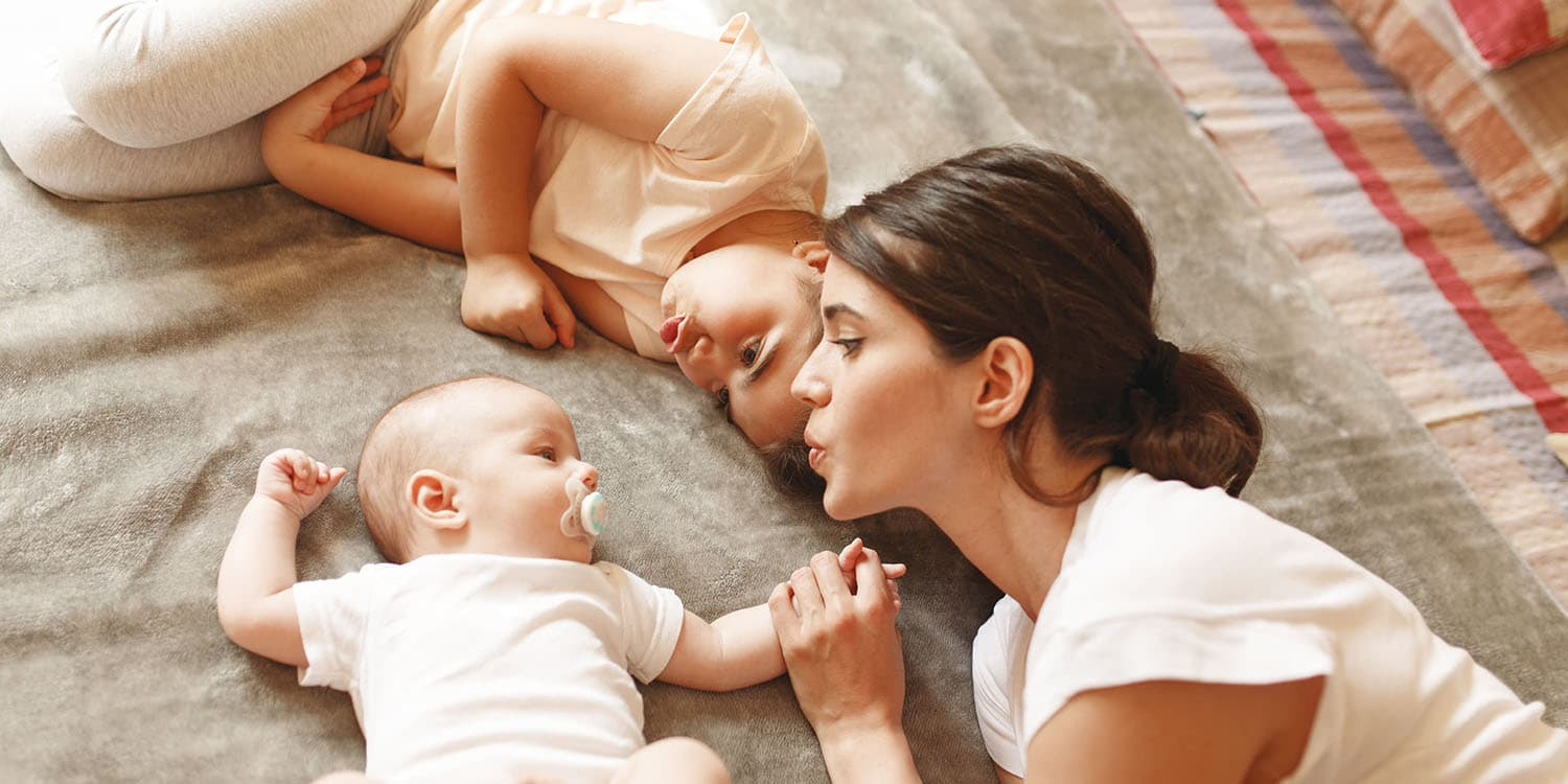 Mother and sibling cuddle with baby, baby has pacifier in mouth