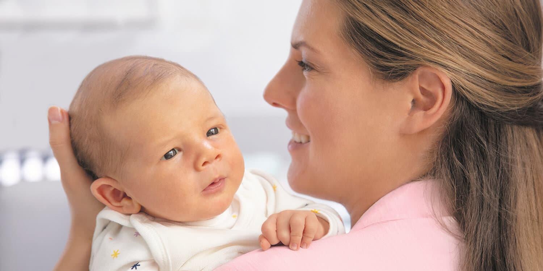 Mamma håller nyfödd på armen och ler