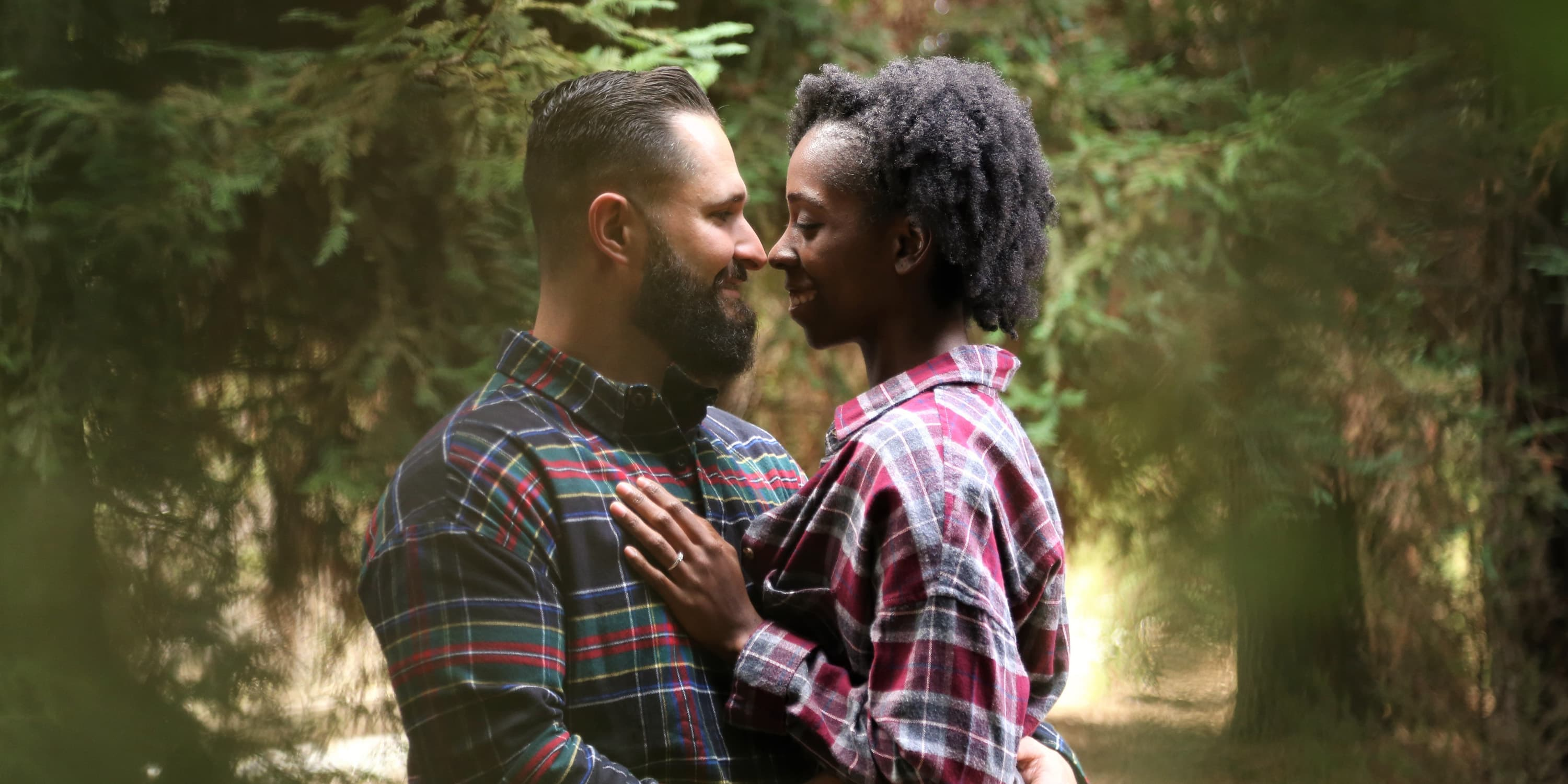 Young couple standing in forest hugging and smiling at each other