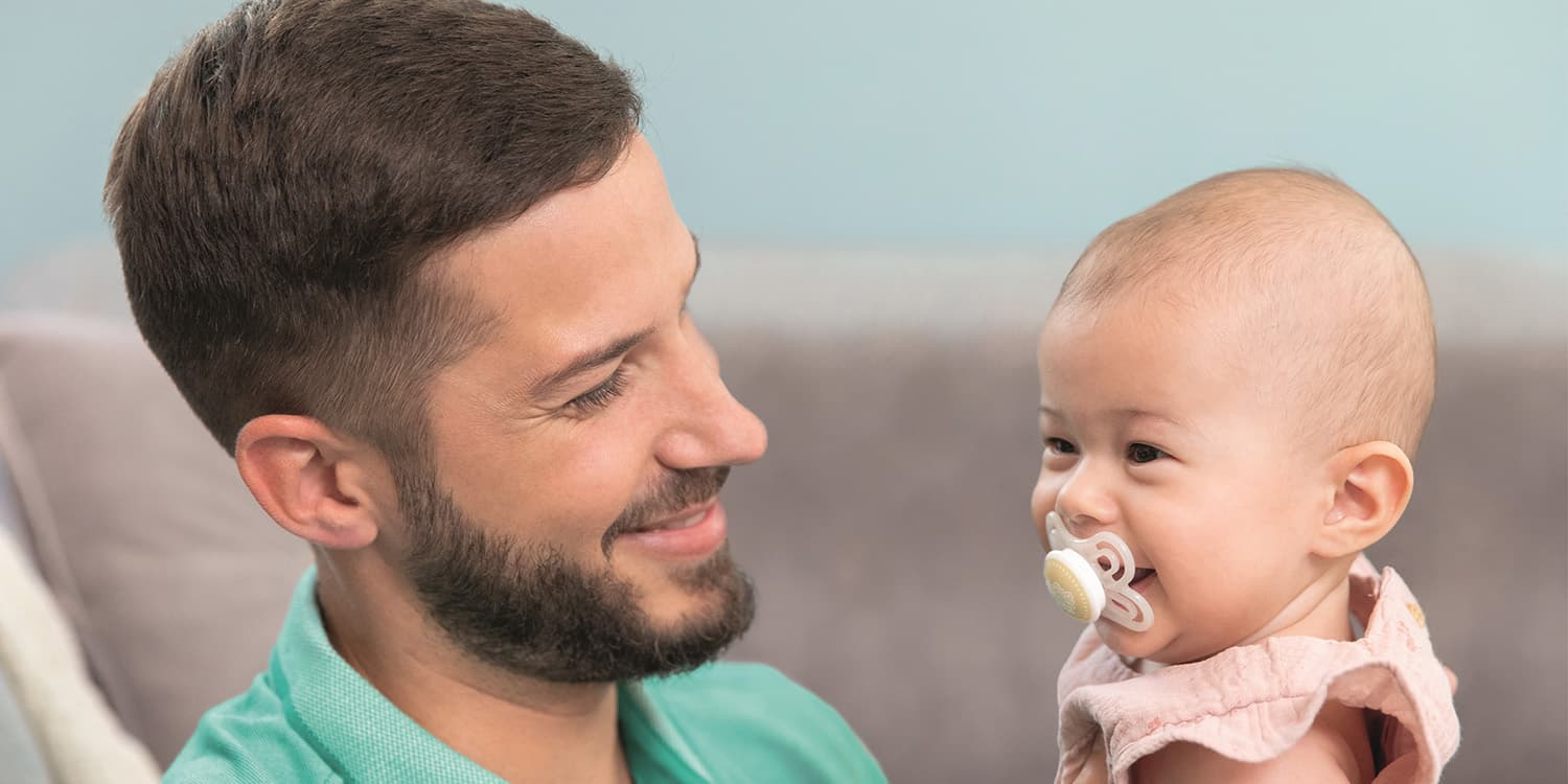 Dad holding baby with pacifier in mouth