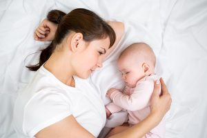 Mamma och baby sover i sängen